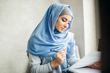 beautiful Muslim woman working with documents. business, lifestyle concept Archivio Fotografico