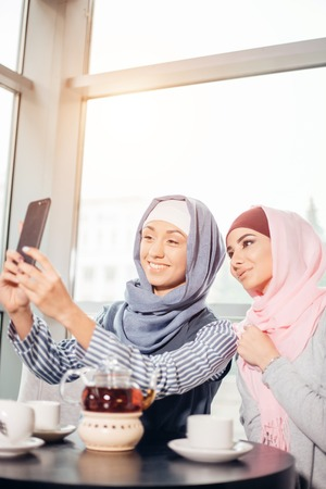 young beautiful muslim woman taking a self portrait with camera phone Standard-Bild