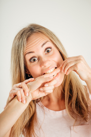closeup portrait picture of woman biting finger of her sister Stock Photo