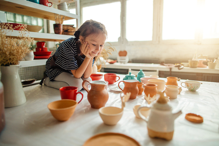 girls in studio are made of many ceramic cups Stock Photo