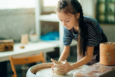 Child sculpts from clay pot. modeling on potter wheel. Archivio Fotografico