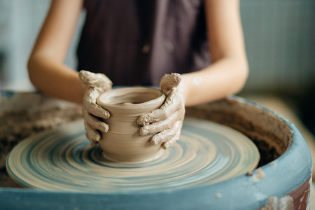 Female potter working at throwing wheel at studio. Clay workshop 版權商用圖片 - 91678840
