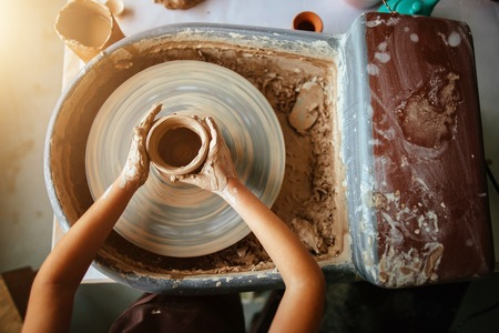 Hands of young potter, close up hands made cup on pottery wheel