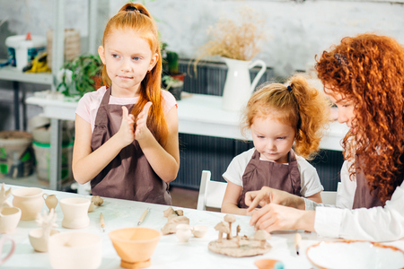 redhead Mother and kid daughter at home molded from clay and play together