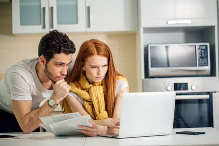 family managing budget, reviewing their bank accounts using laptop in kitchen