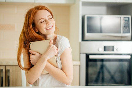 girl cuddling a tablet and looking above on a white wall Stock Photo