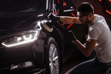 Car detailing - man with orbital polisher in auto repair shop. Selective focus. Foto de archivo