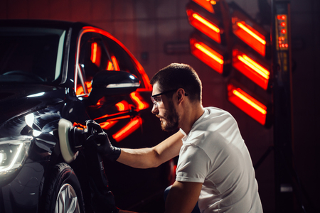 Car detailing - man with orbital polisher in auto repair shop. Selective focus. 스톡 콘텐츠