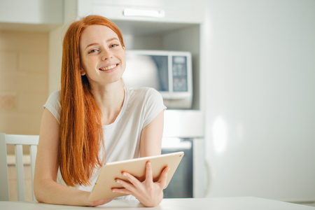 happy young woman holding tablet and looking at camera