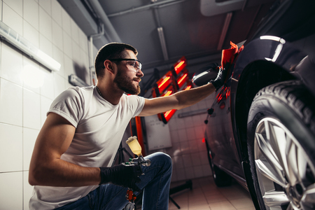 man cleaning car with microfiber cloth, car detailing or valeting concept Archivio Fotografico