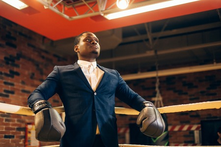 person wearing business suit and boxing gloves. Stock Photo