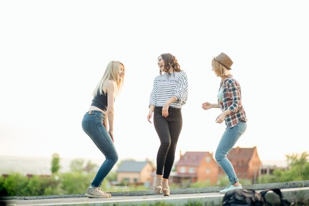 three happy joyful young women jumping and laughing together at park