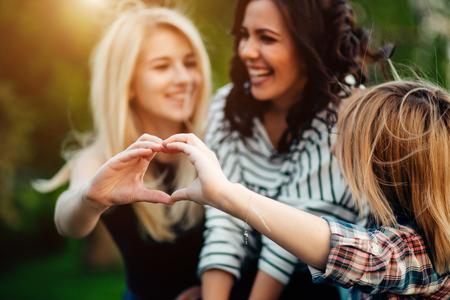 three female friends making heart shape from hand