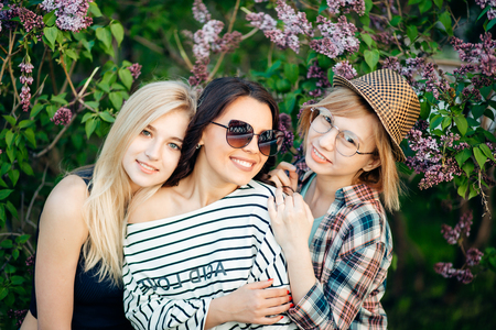 three confident casual women standing at park and looking at camera