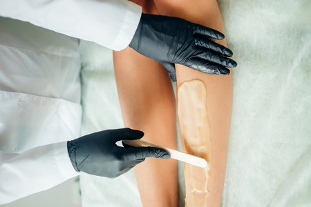 close up Beautician waxing female legs in spa center