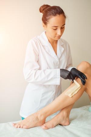 Beautician waxing woman a leg at salon. Depilation. Stock Photo