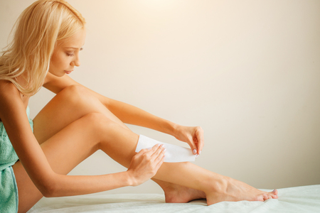 Long Woman Legs With Wax Strip On. Closeup Of Female Depilates Her Long Legs Stock Photo