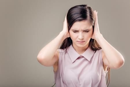 Jonge vrouw die haar oren behandelt. Hoor geen kwaad concept Stockfoto