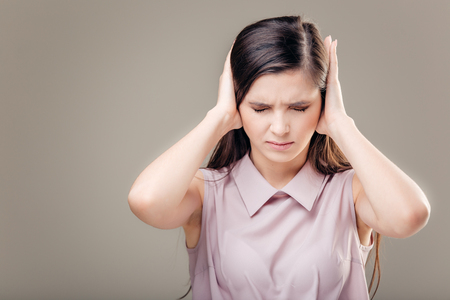 Young woman covering her ears. Hear no evil concept