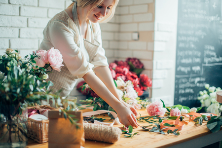Florist workplace: woman arranging a bouquet with flowers 스톡 콘텐츠