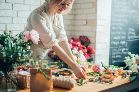 Florist workplace: woman arranging a bouquet with flowers Banque d'images