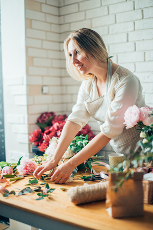 Cute concentrated young female florist in glasses working in flower shop Stock Photo