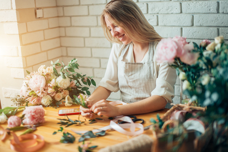Florist at work: pretty young blond woman making bouquet of different flowers