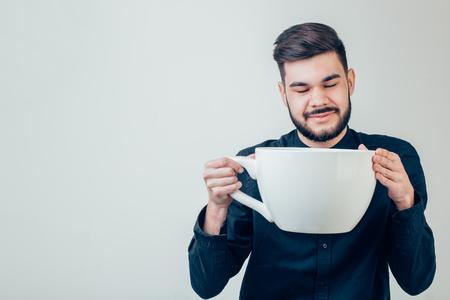 カフェインで黒いコーヒーの面白い巨大で特大のカップを保持しているビジネスマン