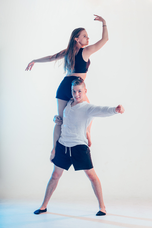 modern style beautiful dancers working out. Young man holding his girl partner