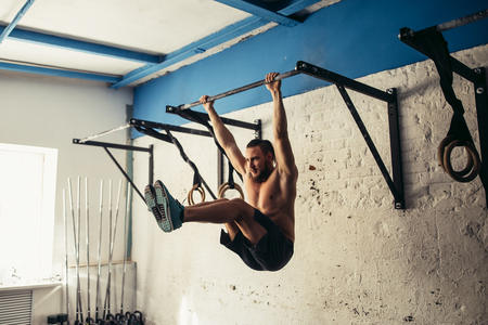 Fit toes to bar man pull-ups bars workout exercise at gym Imagens