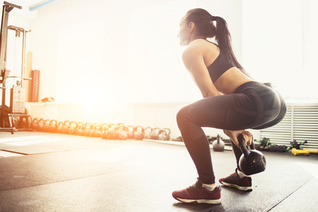 Young fitness woman lifting heavy weight kettle bell at gym