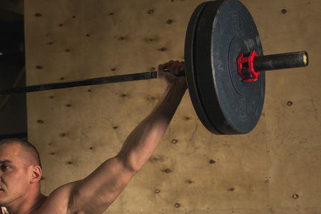 brutal muscular man with beard train with barbell raised over head in gym