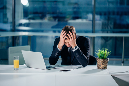 Stressed businessman having problems and headache at work
