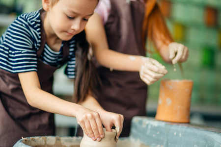 pottery workshop - girls sculpts from clay on pottery wheel