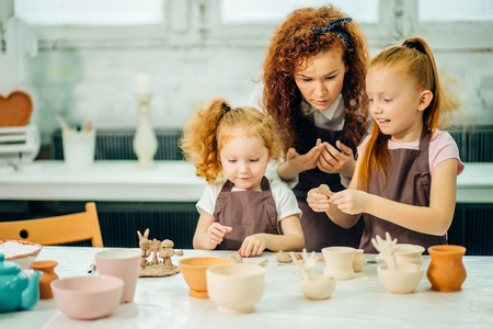 redhead mother and two daughter mold with clay, pottery children