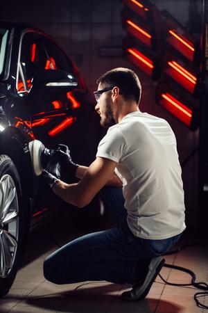 Car polish wax. worker hands holding a polisher