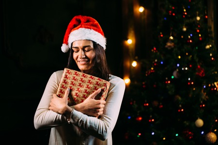 smiling woman in santa helper hat with many gift boxes Stock Photo