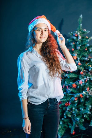 girl in santa hat near a christmas tree with gifts