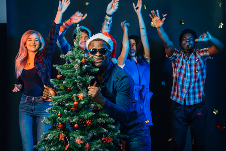 african american man hugging with cristmas tree Stock Photo