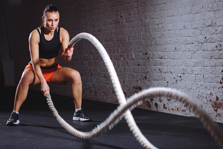 Athletic woman doing battle rope exercises at gym