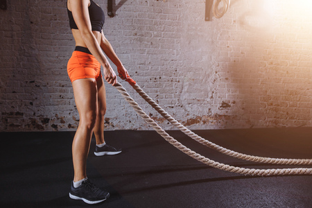 Young woman preparing to working out with battle ropes in cross fit gym