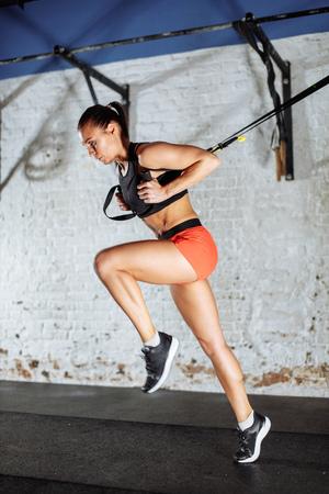 Trx の概念。サスペンショントレーナースリングの助けを借りて彼女の筋肉を行使する女性