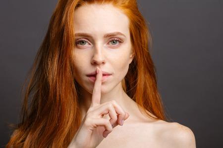 girl holding index finger at her lips, saying shh