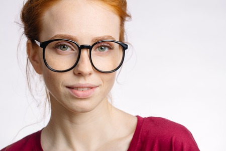 portrait of attractive young redhead woman smiling with glasses