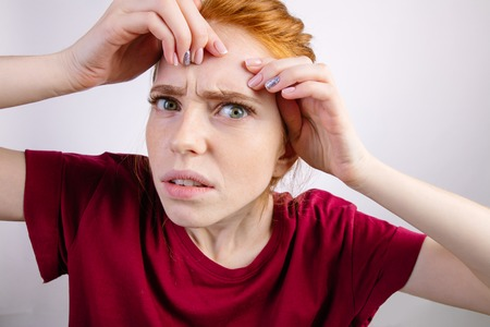 redhead woman squeezing her pimples, removing pimple from her face Stock Photo