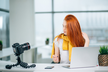 young woman broadcasting a hair tutorial for her video blog