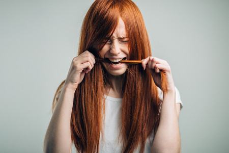 Sad redhead girl bite her damaged hair.