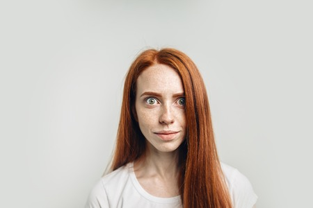 redhead girl with healthy freckled skin looking at camera