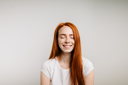 Beautiful ginger girl smiling posing with closed eyes
