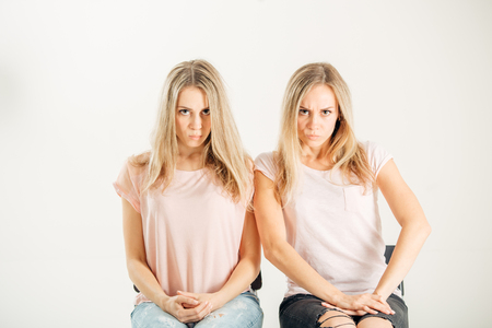 young serious sisters twins on a white background Stock Photo